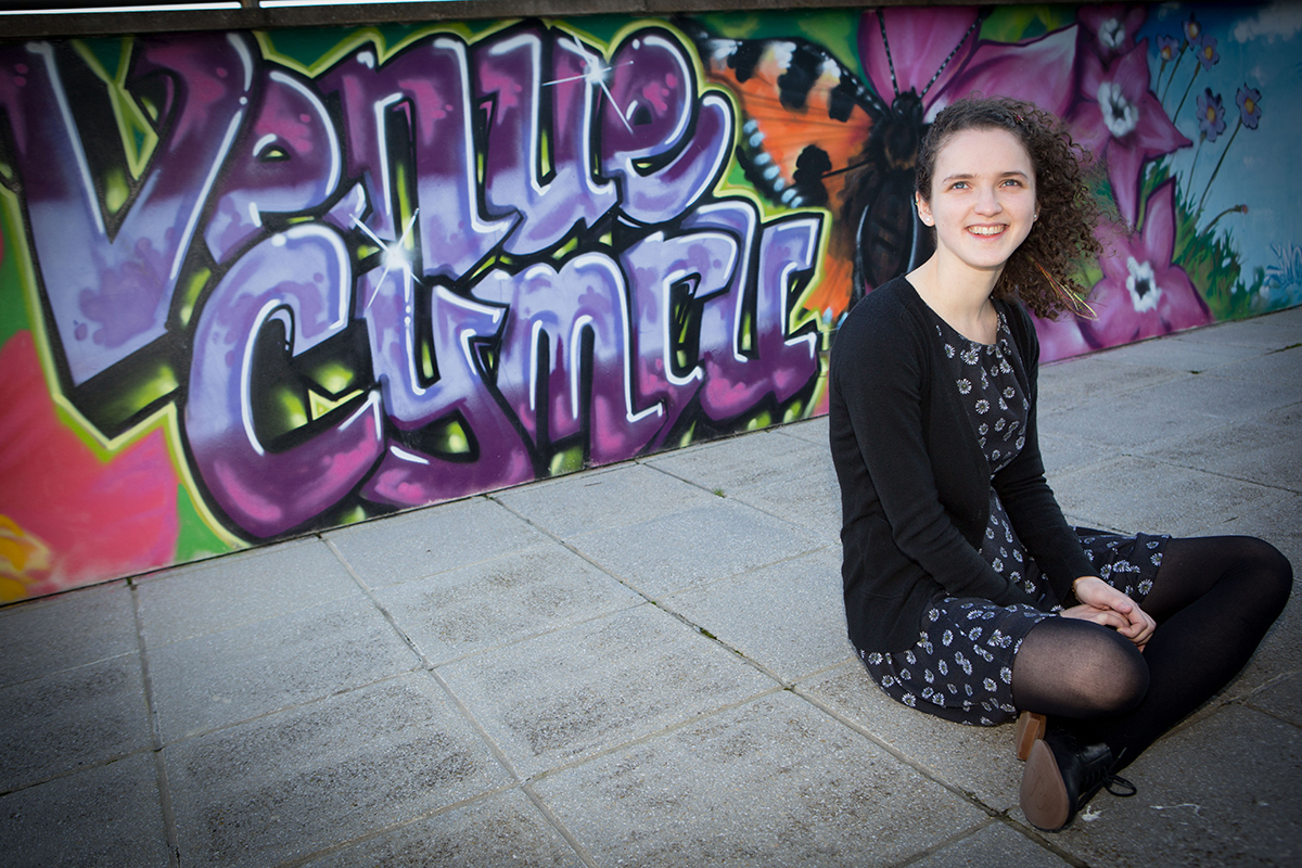 Venue Cymru, Llanddudno. New Creative Intern Hephzibah Leafe at Theatre. Pictured: Outside the venue next to some grafitti